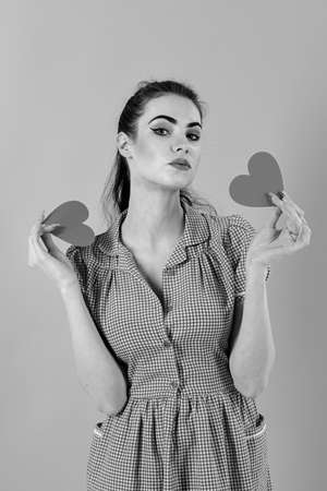Dating, relationship, beauty concept. Girl smiles with valentine hearts isolated on pink. Girl with serious face, make up and red hearts. Woman in stylish dress holds romantic symbols. Full of love