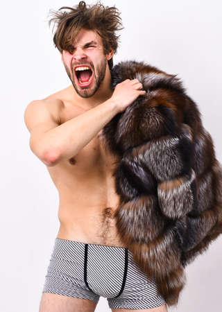 Richness and luxury concept. Bachelor rich lover. Guy attractive posing fur coat on body. Luxury lifestyle and wellbeing. Sexy sleepy macho tousled hair isolated on white. Luxury status symbol