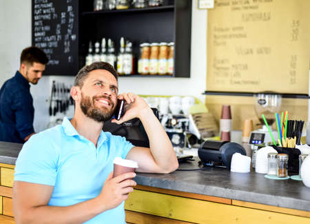 Man mobile conversation cafe barista background. Drink coffee while waiting. Waiting for you. Man smartphone order coffee in cafe. Coffee break concept. Coffee take away option for busy people