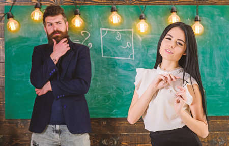 Man with beard and young lady teacher stand in classroom, chalkboard on background. Generation concept. Lady teacher and bearded hipster schoolmaster working together in school