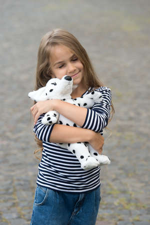 Because your baby deserves care. Happy child cuddle toy dog outdoors. Love and care. Play and development. Toy shop. Sharing happiness