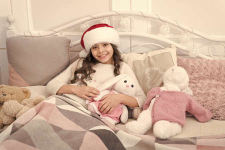 Cozy room. Child waiting christmas in bedroom. Kid lay in bed relaxing. Home is best place in world. Girl little kid relaxing on bed light interior with christmas decorations. Christmas eve concept