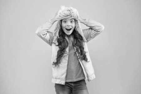I cant believe in it. fur earflap hat accessory. small girl winter hat. warm clothes for cold season. kid fashion. girl look like hipster. happy kid pink background. autumn style. Childhood activity