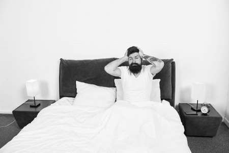 Hangover effect. Hipster got terrible headache in morning. Bearded man suffer from headache in bed. Headache attack. Migraine or tension headache. Cold and flu symptoms. Kill pain. Treat disease.