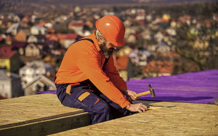 Construction Industry and Waterproofing. roofer working on roof structure of building on construction site. roofer wear safety uniform inspection. Roofer working. Roofer working tool Zdjęcie Seryjne