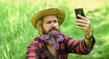 Countryman making selfie on phone. protect green environment. Agriculture farmer rest after day work. Worker in rural farm. farmer with lilac flower in beard. Ecology. Green field in summer