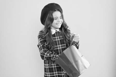 Receiving gift. Adorable small child taking up surprise gift on yellow background. Cute little girl holding shopping bag with present. Gift shop. Gift delivery service Stockfoto