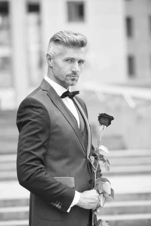 Make good first impression. Valentines day and anniversary. Handsome guy rose flower romantic date. Well groomed macho tailored suit. Romantic gentleman. Man mature confident macho with romantic gift