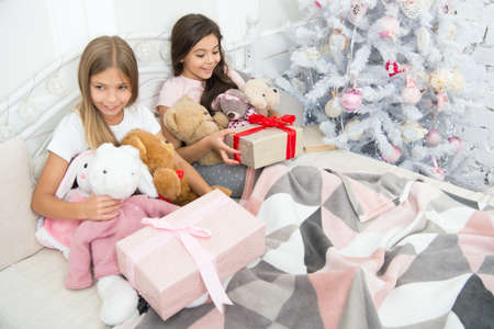 Small children in bedroom with gift. Kindness concept. Christmas atmosphere. Making surprise. Wrapped present. So touched with gift. Small girls bed on Christmas eve. Happy children Christmas spirit