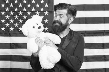 4th of July. Independence day. American guy with toy celebrate holiday. American holiday. Man bearded hipster hold teddy bear american flag background. Child care. Still childish. Infant and funny