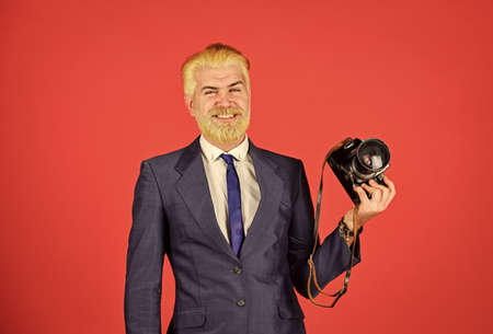 Young expertise. vintage camera. happy businessman hold retro camera. mature man dyed beard and hair. professional photographer make photo. male beauty. capture result of barbershop salon