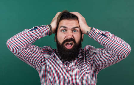 brutal bearded man wear casual checkered shirt has headache. express human emotions. caucasian hipster on green background. shocked mature teacher on background of blackboard Standard-Bild