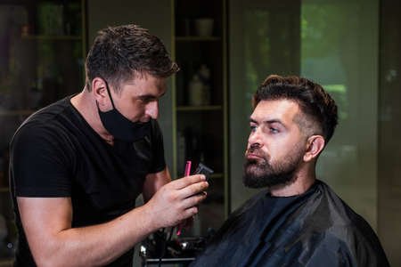 attractive barber making haircut of handsome guy in barbershop, hairdressing tools