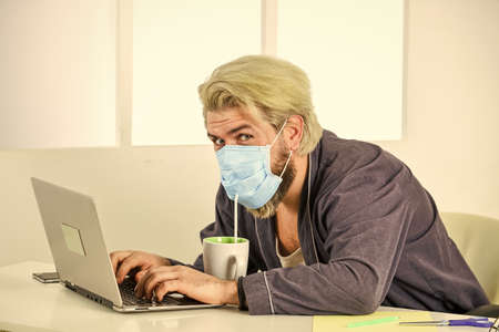 Home office. Wearing mask protect from coronavirus. Man in mask drink tea coffee using straw. Serious hygiene. Remote job. Worker in medical mask. All you need for productive day. Totally protected