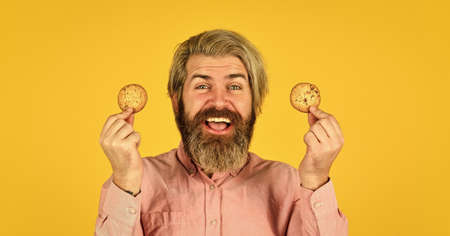 man on dieting. bearded hipster hold biscuit. full of calorie. concept of harmful food. pastry and dessert. bakery shop advertisement. homemade chocolate chip cookies Standard-Bild
