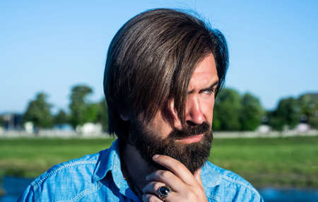brutal bearded guy with moustache having stylish haircut and wear casual shirt outdoor, summer