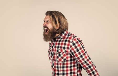 feel huge anger. angry bearded man in checkered shirt shouting. Portrait of bearded hipster. guy with long lush beard and mustache on face. handsome confident man has perfect hairstyle Standard-Bild