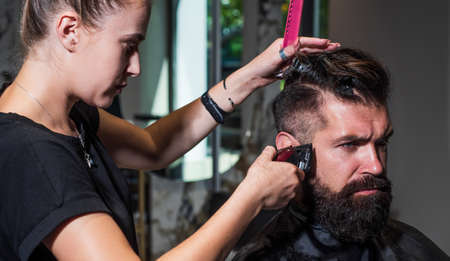 Style in action. brutal hipster with moustache making new hairstyle. barbershop. male trendy hairdo. perfect haircut with blade razor. barber master cut hair. mature hipster with beard at hairdresser