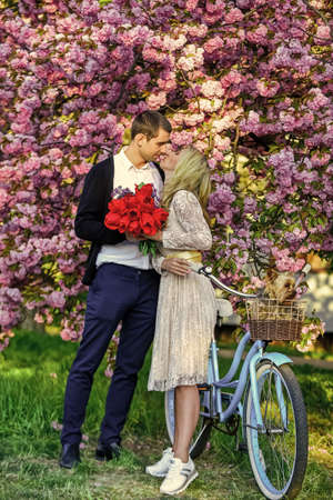 Real love. romantic season. dog in vintage bike. Love and friendship. couple in love under tree valentines day. newlyweds hug at blooming pink sakura. spring fashion and beauty. togetherness