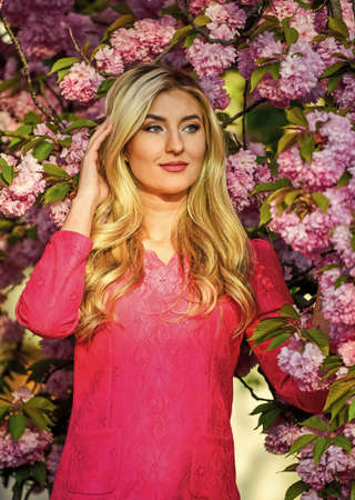 Girl cherry flower blossom. Spring fashion collection. Woman spring flower sakura bloom background. Blonde woman in garden. Femininity. Sakura tree blooming. Pink mood. Sakura season. Gorgeous girl Banque d'images