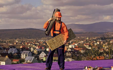 Roof installation. Man hard hat work outdoor. Building house. Roof Mechanic concept. Removing hazards. Inspect repair and replace. Fix or build. Provide safe access to roof. Roofer repair roof Zdjęcie Seryjne