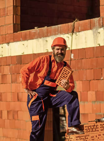 build your own future. happy bearded man hold brick. brickwork. Man takes brick from the pile. Male construction worker holding brick. Repairman guy hard build up new layer level Zdjęcie Seryjne