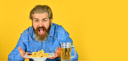 guy in american bar drinking beer glass and eating potato. Cheers. watching football on TV. american fast food. happy bearded man with beer and french fries. French fries potato. copy space
