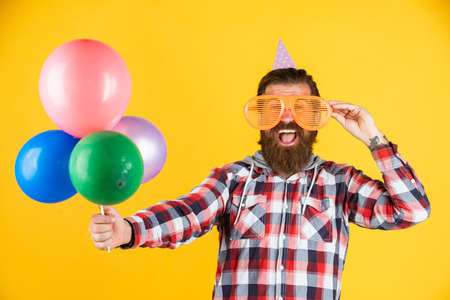 Young and carefree. Party Elements and holiday objects. Multi colored fun. best party for retirement. cheerful man with beard and moustache. hipster smiling with balloon. Celebrating happy party Standard-Bild