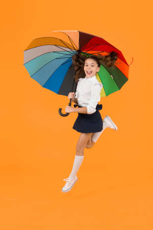 Energetic look. Adorable girl jumping with autumn look on yellow background. Cute little schoolchild having glamour look with colorful umbrella. School look of small child