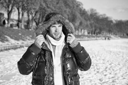 Travel and vacation concept. Winter outfit. Guy jacket hood. Man warm jacket snowy nature background. Wind resistant clothes. Winter favorable weather conditions. Sunny winter day. Winter menswear
