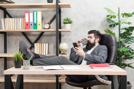 Coffee is pledge of successful negotiations. Caffeine addicted. Mobile call. Start day with coffee. Coffee relaxing break. Boss enjoying energy drink. Man bearded businessman hold cup and smartphone