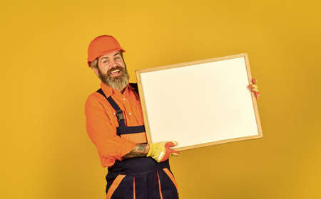 professional repairman in helmet. Engineer project, copy space. architect and engineering drawing. contractor giving presentation. Presentation on flipchart plan. Happy Builder man with flipchart
