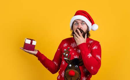 happy bearded man in santa claus hat and knitted sweater with gift box celebrate new year winter holiday, christmas shopping