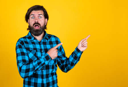 surprised handsome hipster in checkered shirt pointing away while standing against yellow background, advertisement Standard-Bild