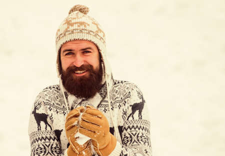 Snow games. Have fun winter day. Cheerful bearded hipster knitted hat and warm gloves play with snow outdoors. Christmas holidays. Making snowball. Happiness concept. Smiling man snow background