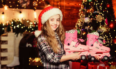 Girl satisfied christmas gift. Christmas gift she dreamed about. Best gift ever. Happy new year concept. Dreams come true. Got gift exactly she wanted. Kid near christmas tree hold roller skates