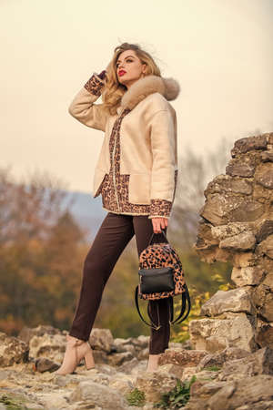 Best journey ever. girl leopard pattern half-length coat. warm short faux fur coat in fall. sexy girl red lipstick nature background. autumn season clothes and accessory. girl long hair hold backpack