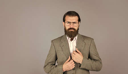 fashionable man wear glasses. formal fashion model. handsome man standing on gray background. serious bearded businessman. stylish mature man looking modern. mens jacket wardrobe. copy space