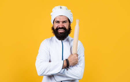man cook armed with wooden rolling pin for cooking, housekeeping