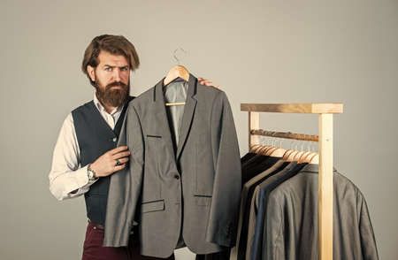 Tailor measures man. stylish business man at workspace. Fashion design studio. Male fashion designer. Individual measures hand of man. Man ordering business suit posing indoor. Another working day