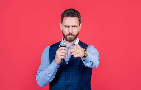 Professional salesman speak into microphone pointing finger red background, presentation