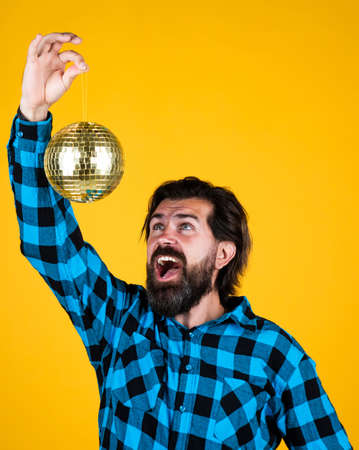 Content man in checkered shirt with happy face holding shining disco ball posing on yellow, party fun