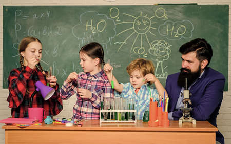 Interests and topic club. Group interaction and communication. Share interests hobbies talents and skills. School club education. Teacher and pupils test tubes in classroom. Chemistry themed club