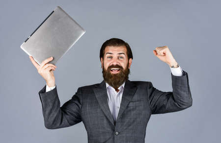 celebrating success. male employee holding finance report and researches in coworking space on laptop. new technology in modern business lie. happy caucasian bearded hipster with computer