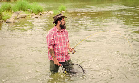 summer weekend. Big game fishing. fisherman with fishing rod. bearded fisher in water. hobby and sport activity. pothunter. mature man fly fishing. man catching fish. Fish Taxi