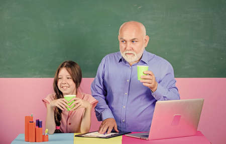 Our school is best. online education. Back to school. little girl with man tutor study on laptop. new technology in learning. school lesson online. Writing an essay. mature teacher help school girl