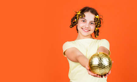 Fancy teen. Hairstyle for disco party. Have fun. Retro party. Child hold golden disco ball. Cheerful girl with disco ball. Fashion kid posing with curlers in hair. Night club. Hairdresser salon
