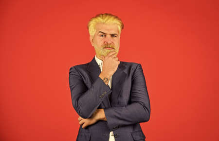 mature businessman making decision. serious and concentrated boss. bearded ceo in formal suit. blond hipster with dyed beard hair. professional business manager. Elegant man stylish costume