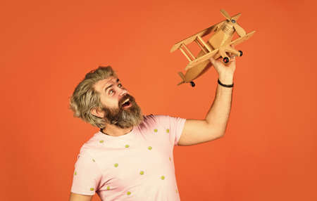 Aviator playing wooden airplane toy. man with wooden plane. fly on airplane. air travel and transportation. having fun. dream and people concept. Gift to a man. future technology