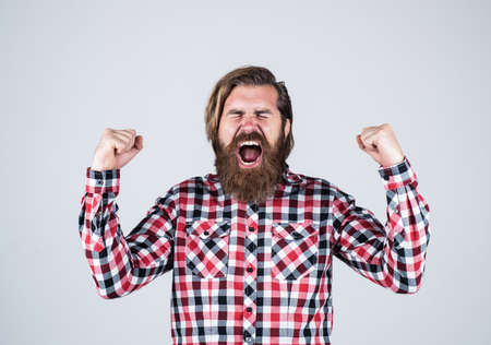 after successful game. successful mature hipster with beard. brutal caucasian guy with moustache. bearded man wear checkered shirt. angry brutal man shouting. male barber care. hair and beard care